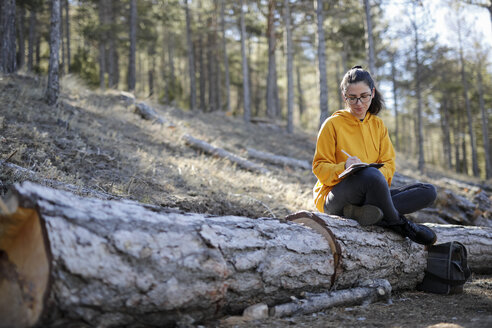 Young woman with yellow sweater in the forest, writing - GRSF00005