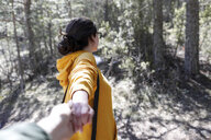 Young girl with yellow sweater holding hand of man in the forest - GRSF00011