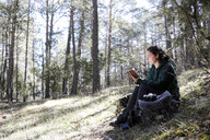 Young woman with yellow sweater in the forest, writing - GRSF00014