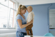 Happy pregnant mother embracing toddler son standing on table - KNSF05205
