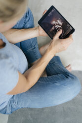 Pregnant woman sitting on the floor looking at ultrasound picture on tablet - KNSF05217