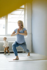 Pregnant woman with toddler son practicing yoga - KNSF05235