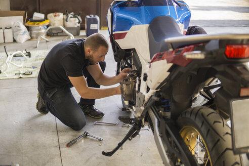 Mechanic working on motorcycle in workshop - FBAF00152