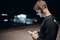 Sportive young man with smartphone and earphones outdoors at night - ZEDF01739