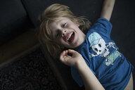 Portrait of exuberant boy lying on couch - JLOF00298