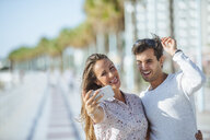 Happy young couple taking a selfie on promenade - KIJF02071