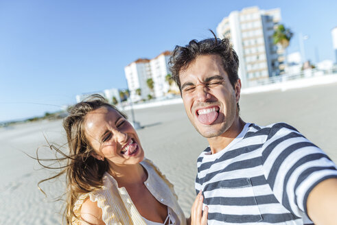 Funny selfie of a happy young couple on the beach - KIJF02077