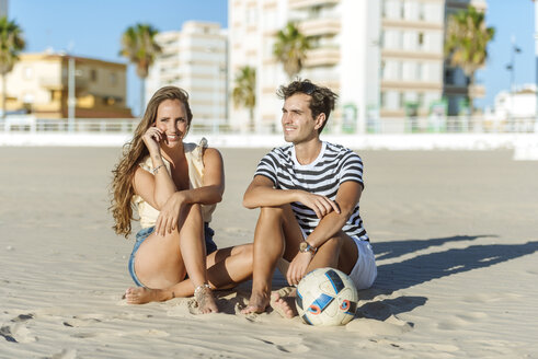 Smiling young couple sitting on the beach with a ball - KIJF02080