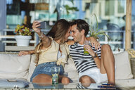 Happy affectionate young couple taking a selfie on the terrace of a bar - KIJF02089