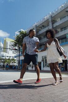 USA, Florida, Miami Beach, happy young couple crossing the street - BOYF00800