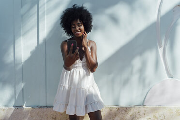 Smiling young woman wearing white dress looking at cell phone at a wall - BOYF00815