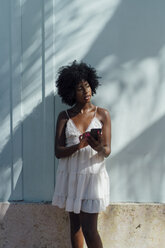 Young woman wearing white dress using cell phone at a wall - BOYF00818