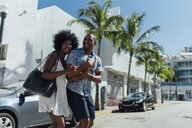 USA, Florida, Miami Beach, happy young couple crossing the street - BOYF00827