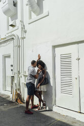 Smiling affectionate young couple standing at building - BOYF00830