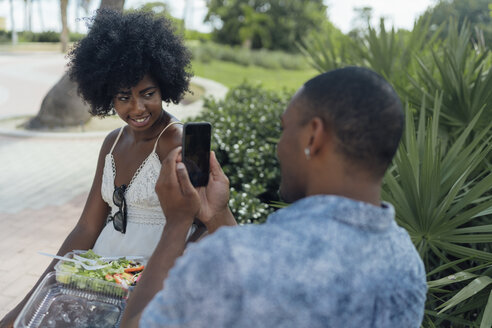 USA, Florida, Miami Beach, young man taking a picture of girlfriend eating a salad in a park - BOYF00857