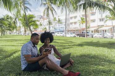 USA, Florida, Miami Beach, young couple using tablet and laptop on lawn in a park - BOYF00860