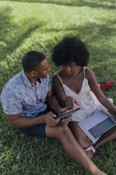 Young couple using tablet and laptop on lawn in a park - BOYF00863