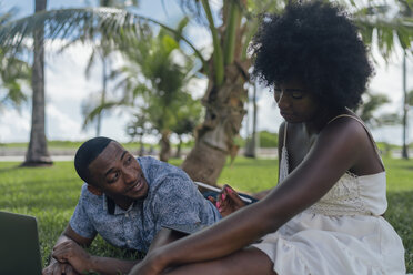 USA, Florida, Miami Beach, young couple using tablet and laptop on lawn in a park - BOYF00869