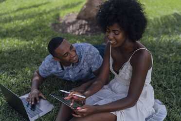 Happy young couple using tablet and laptop on lawn in a park - BOYF00872