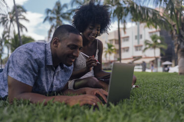USA, Florida, Miami Beach, smiling young couple using tablet and laptop on lawn in a park - BOYF00878