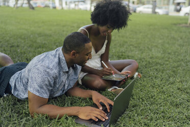 Young couple using tablet and laptop on lawn in a park - BOYF00881