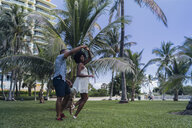 USA, Florida, Miami Beach, happy young couple dancing in a park in summer - BOYF00884