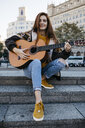 Red-haired woman playing the guitar in the city - JRFF01920