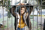 Red-haired smiling woman behind fence - JRFF01926