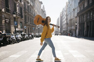 Red-haired woman with a guitar on zebra crossing - JRFF01938