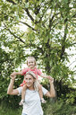 Happy mother carrying daughter piggyback in nature - HMEF00048