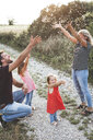 Happy family with two daughters playing with confetti on a field path - HMEF00057