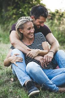 Happy couple sitting on a meadow - HMEF00063