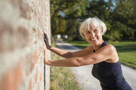 Smiling sportive senior woman leaning against a brick wall - DIGF05429