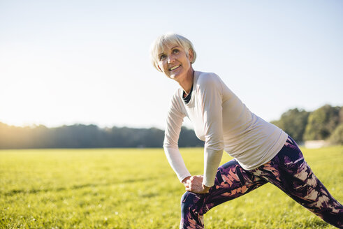 Smiling senior woman stretching on rural meadow - DIGF05432