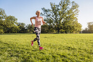 Senior woman running on rural meadow - DIGF05447