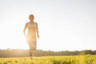 Senior woman running on rural meadow at sunset - DIGF05459