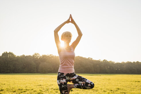 Senior woman doing yoga on rural meadow at sunset - DIGF05462