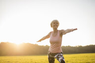 Senior woman doing yoga on rural meadow at sunset - DIGF05465