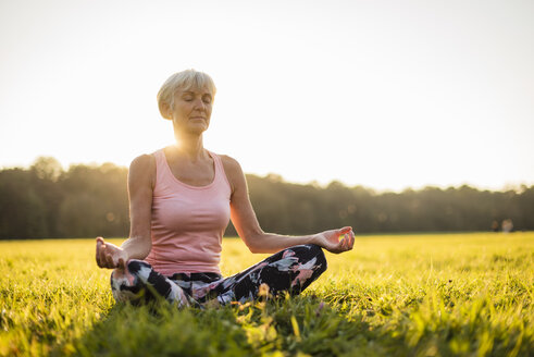 Senior woman in lotus position on rural meadow at sunset - DIGF05468