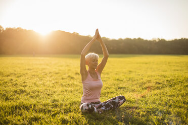 Senior woman doing yoga on rural meadow at sunset - DIGF05471