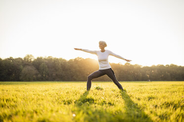 Senior woman doing yoga on rural meadow at sunset - DIGF05474