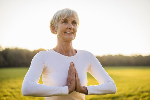 Senior woman doing yoga on rural meadow at sunset - DIGF05477