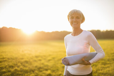 Portrait of smiling senior woman holding yoga mat on rural meadow at sunset - DIGF05480