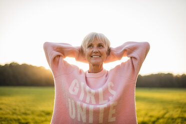 Portrait of confident senior woman standing on rural meadow at sunset - DIGF05483