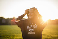 Smiling senior woman wearing a hoodie standing on rural meadow at sunset - DIGF05486