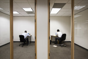 A view of two businessmen working on opposite sides of a wall in two different office spaces. - MINF09546