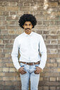 Mid adult man standing in front of brick wall, hands in pockets - JRFF01976