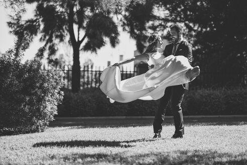 Bridal couple enjoying wedding day in a park - JSMF00564