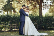 Bridal couple standing head to head with eyes closed in a park - JSMF00567