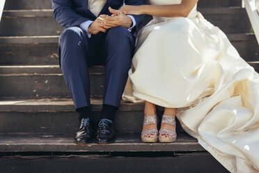 Bridal couple sitting on stairs outdoors, partial view - JSMF00573